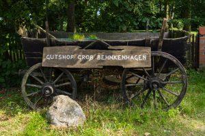 Ein alter Pferdewagen mit Schild mit Aufschrift Gutshof Groß-Behnkenhagen